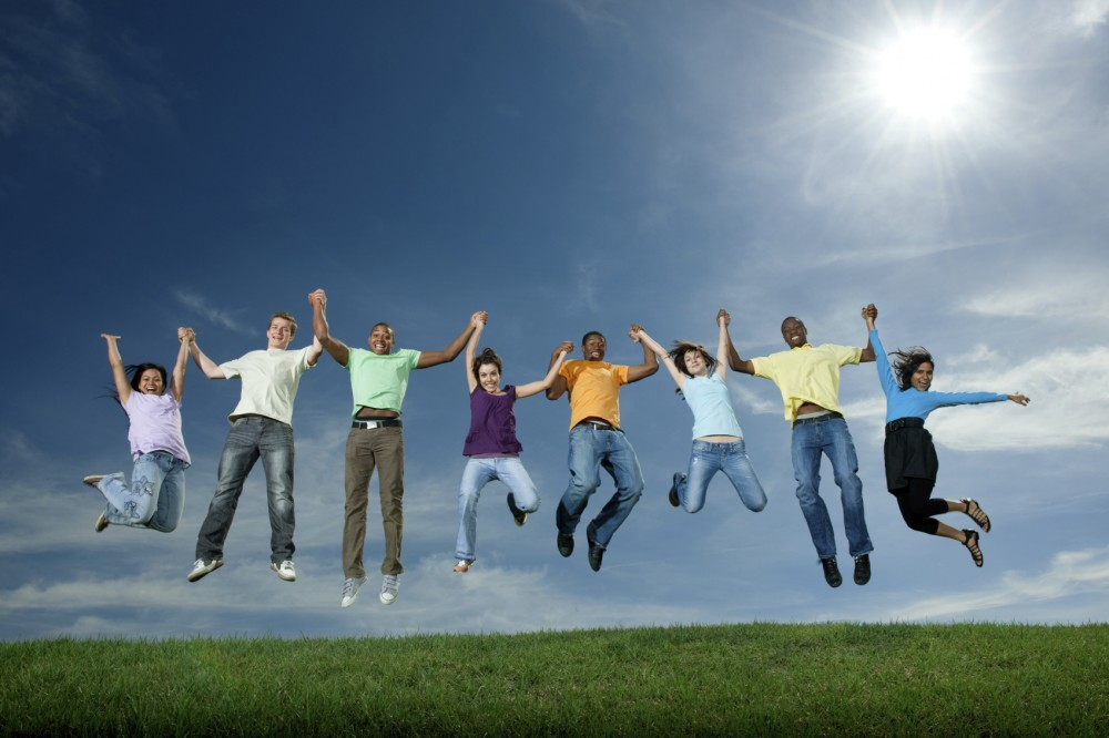 A group of young adults jumping on the hill top. Motion blure in hands and feet. Sun flares in sky.